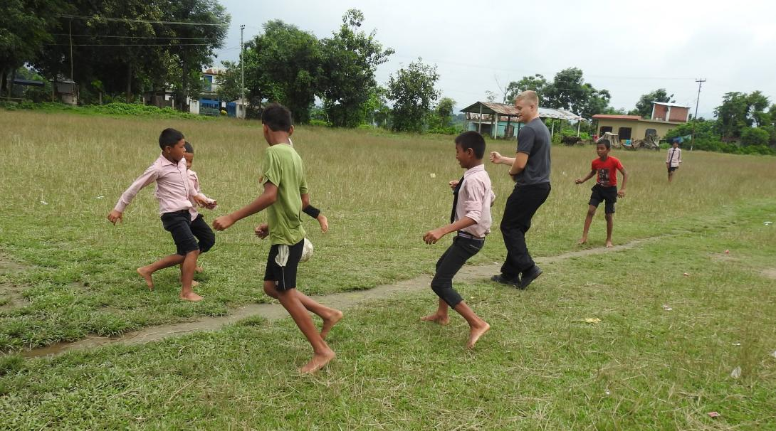Volunteer plays football with students at his Youth Empowerment Project in Nepal.